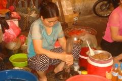 Vietnam, femme qui écrase au pilon pour faire une pâte